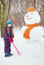 Girl with shovel stands next to big snowman plastic in winter park Stock Photos