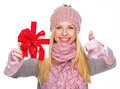 Girl showing christmas presenting box and showing thumbs up smiling in winter clothes Royalty Free Stock Images