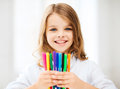 Girl showing colorful felt tip pens education and school concept little student at school Stock Photos
