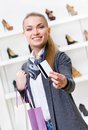 Girl showing credit card in footwear shop with great variety of stylish shoes Stock Photo