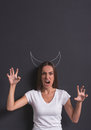 Girl showing devil beautiful young is claws looking at camera and growling standing against blackboard with x s Royalty Free Stock Images