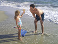Girl showing father starfish on beach Royalty Free Stock Photo