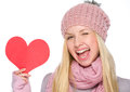 Girl showing heart shaped postcard portrait of in winter clothes and winking Stock Photography
