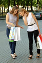 Girl shows her friend that she bought two girls with shopping bags on the street Stock Photo