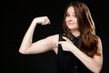 Girl shows her muscles strength and power woman long hair black background concept Stock Image