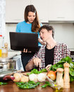 Girl shows the new recipe on laptop during dinner cooking Stock Image