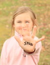 Girl with sign stop on hand kid smiling written palm of her Royalty Free Stock Photography