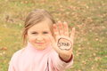 Girl with sign stop on hand kid smiling written palm of her Royalty Free Stock Photo