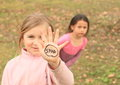 Girl with sign stop on hand kid smiling written palm of her guarding another that is scared Royalty Free Stock Photo