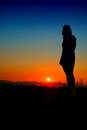 Girl silhouette at sunset with blue sky Stock Photography