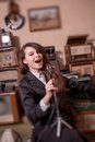 Girl singing in antique shop young with old microphone stand Stock Photography