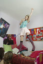 Girl singing in front of friends jumping on bed and at home Royalty Free Stock Photography