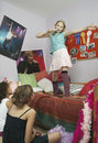 Girl singing in front of friends standing on bed and at home Royalty Free Stock Image