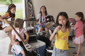 Girl singing into microphone with friends playing musical instrument portrait of cute young in garage Royalty Free Stock Image