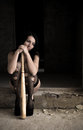 The girl sits with a baseball bat in destroyed building Stock Photography