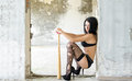 The girl sits with a baseball bat in destroyed building Royalty Free Stock Images