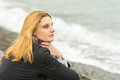 Girl sits on the beach on a cloudy day in cold weather and looking thoughtfully into the distance Royalty Free Stock Photo