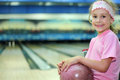 Girl sits and holds ball in bowling club Stock Image