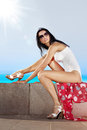 Girl sits on quay beautiful in white swimming suit and takes sun bath Royalty Free Stock Images
