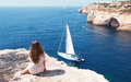 Girl sits on the rock and looks at yachts at ocean Stock Images