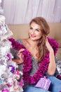 Girl sits on sofa near Christmas tree. Royalty Free Stock Photo