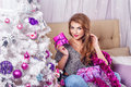 Girl sits on a sofa near the Christmas tree. Royalty Free Stock Photo