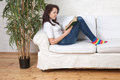 Girl sits on a soft divan and reads a book Royalty Free Stock Photos