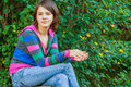 Girl sits on stub teenager in striped jacket with hood big which is bank of lake Royalty Free Stock Images