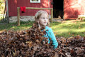 Girl sits up from hiding in leaves Royalty Free Stock Images