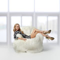 Girl sitting in arm-chair Royalty Free Stock Photo