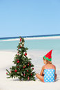 Girl sitting on beach with christmas tree and hat relaxing Royalty Free Stock Photo