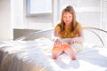 Girl sitting on the bed lying by window Royalty Free Stock Photography