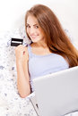 Girl sitting in bed and shopping online with credit card onlineshop ecommerce Royalty Free Stock Photography