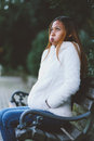 Girl sitting on bench in the city park in cold weather Royalty Free Stock Photo