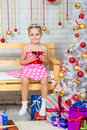 Girl sitting on a bench with a gift in his hand a snowy Christmas trees Royalty Free Stock Photo