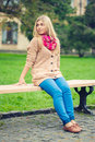 Girl sitting on bench outdoors Stock Photo