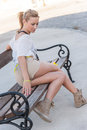 Girl sitting on a bench young and beautiful the and posing outdoors with sunflower Royalty Free Stock Photo