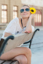 Girl sitting on a bench young and beautiful the and posing outdoors with sunflower Stock Photos