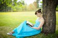 Girl sitting with book near tree Royalty Free Stock Photography