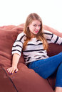 Girl sitting on a braun beanbag chair.