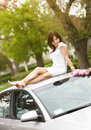 Girl sitting on a car roof Royalty Free Stock Photos