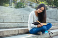 Girl sitting on the city stairs and reading book outdoors Royalty Free Stock Photo