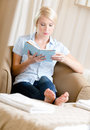 Girl sitting on the couch reads a book concept of education and useful pastime Royalty Free Stock Photography
