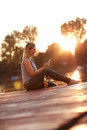 Girl sitting on dock at sunset and looking at phone Royalty Free Stock Photo