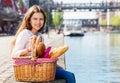 Girl sitting on embankment with picnic basket