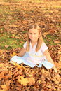 Girl sitting in fallen leaves small kid smiling blond with long hair on autumn Royalty Free Stock Photography