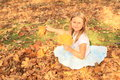 Girl sitting in fallen leaves small kid smiling blond with long hair with maple hand on autumn Royalty Free Stock Images