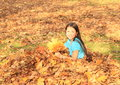 Girl sitting in fallen leaves small kid smiling brunette with long hair with maple hand on autumn Stock Photos