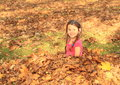 Girl sitting in fallen leaves small kid smiling with long braids on autumn Stock Photography