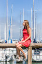 Girl sitting on fence pretty blond haired teenage in red dress a beside a yachting marina Royalty Free Stock Photos